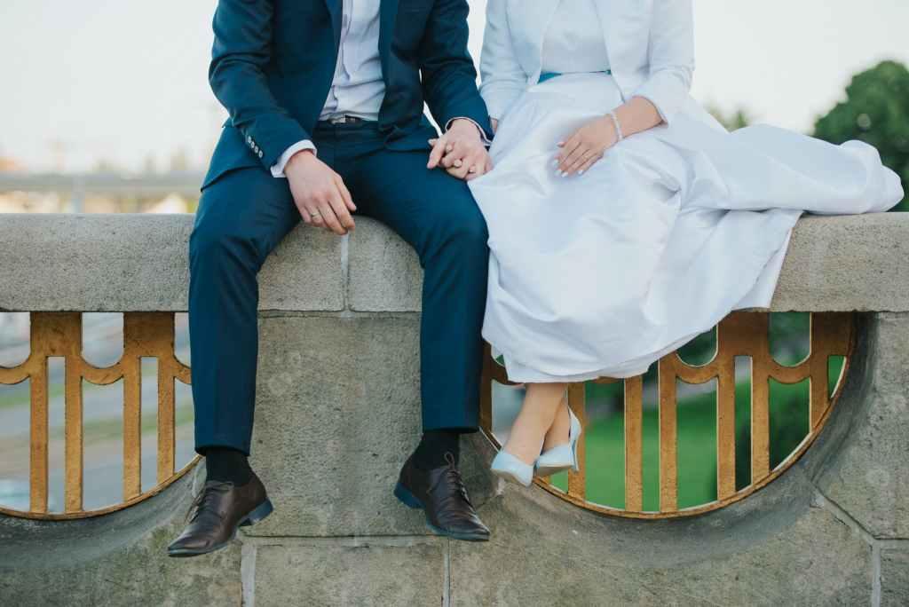 crop faceless newlyweds sitting on railing
