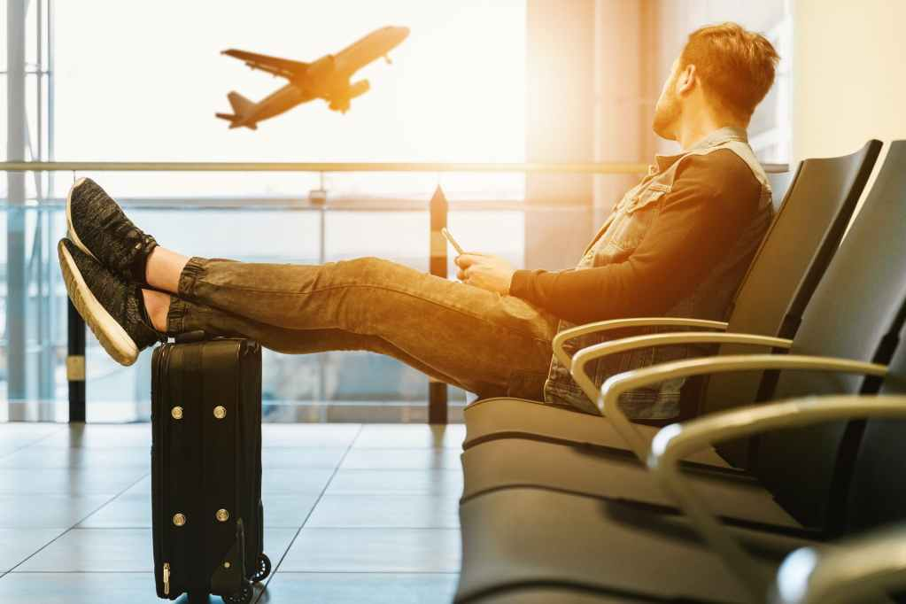 man in airport waiting for boarding on plane