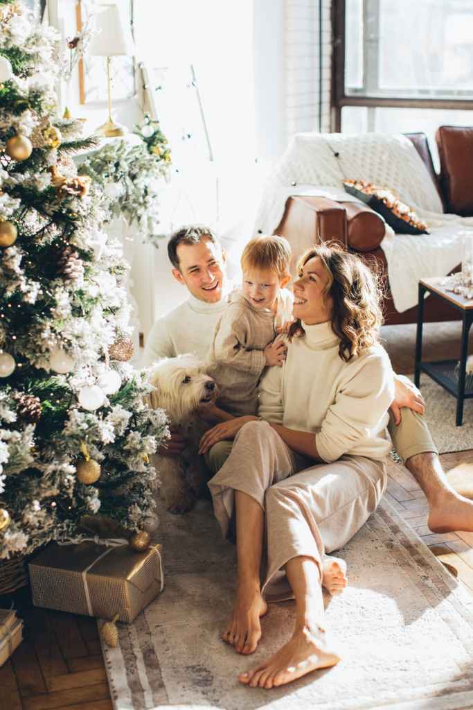 a happy family sitting beside a christmas tree