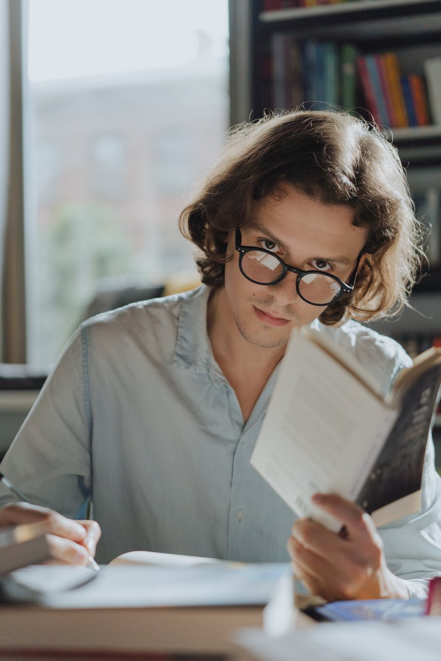 woman in gray dress shirt holding white tablet computer