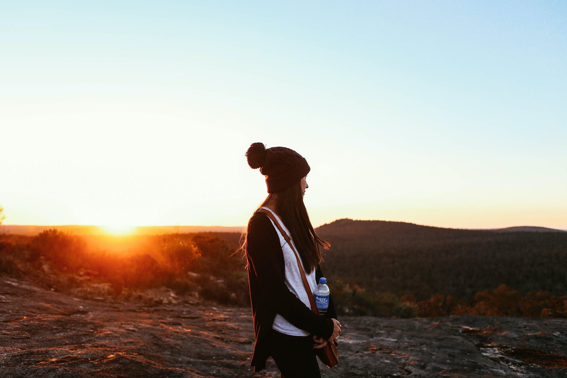 faceless woman standing on hilly valley at sunset