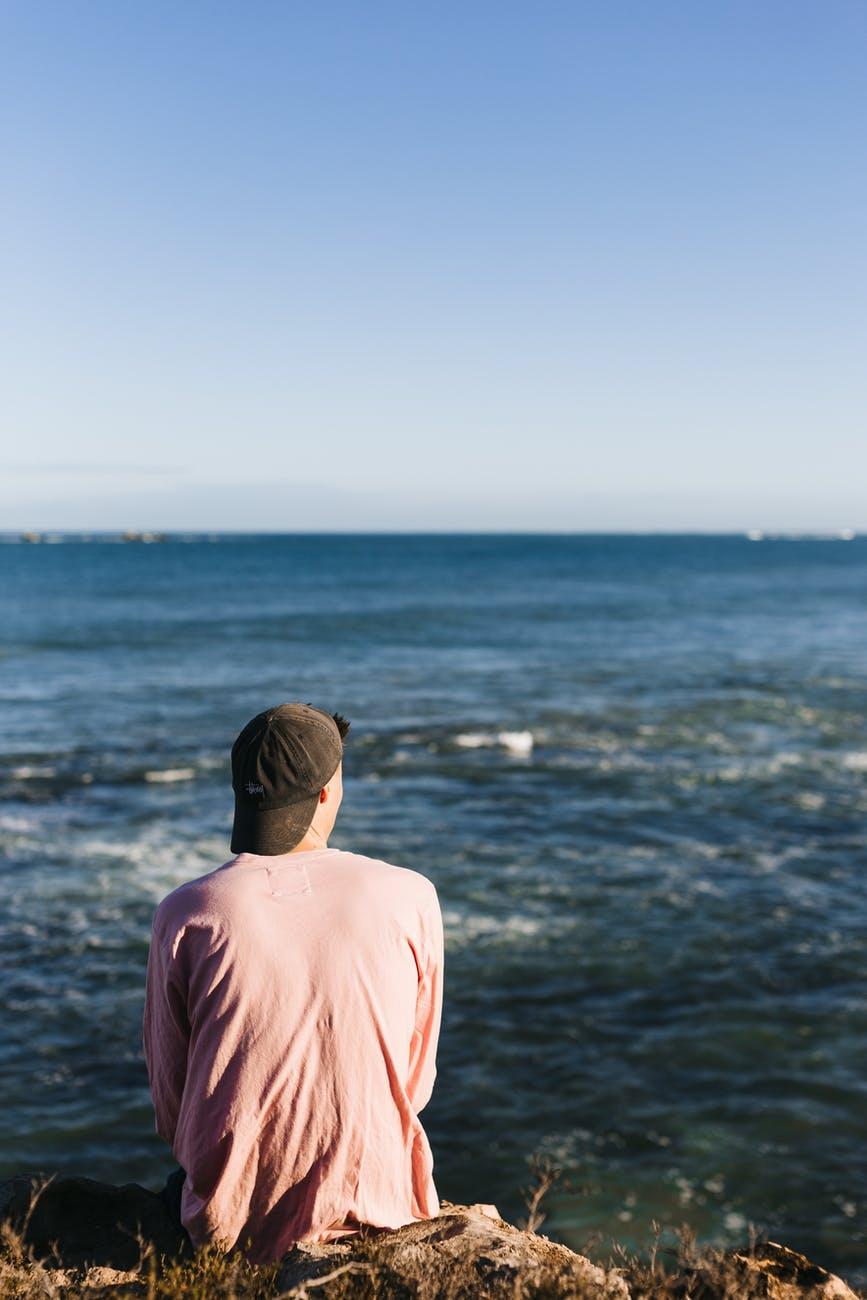 anonymous man sitting on stony seacoast