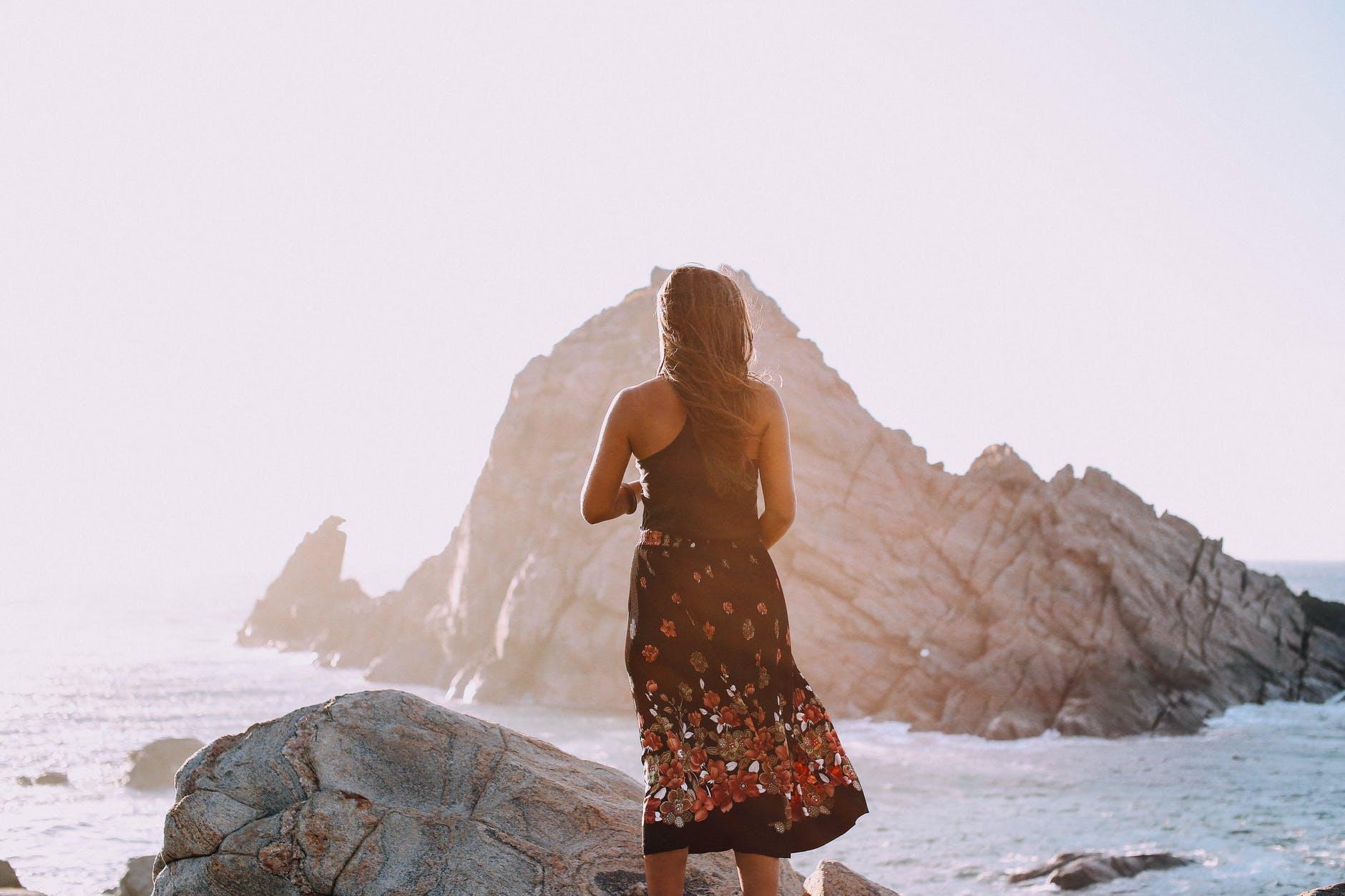 unrecognizable stylish woman standing on rocky seashore