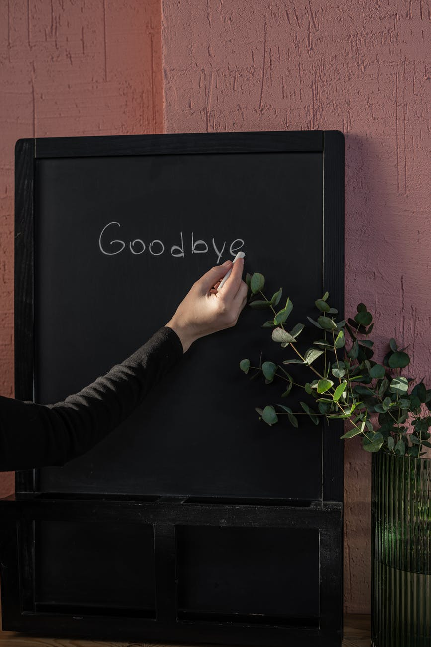 person writing on black board with chalk