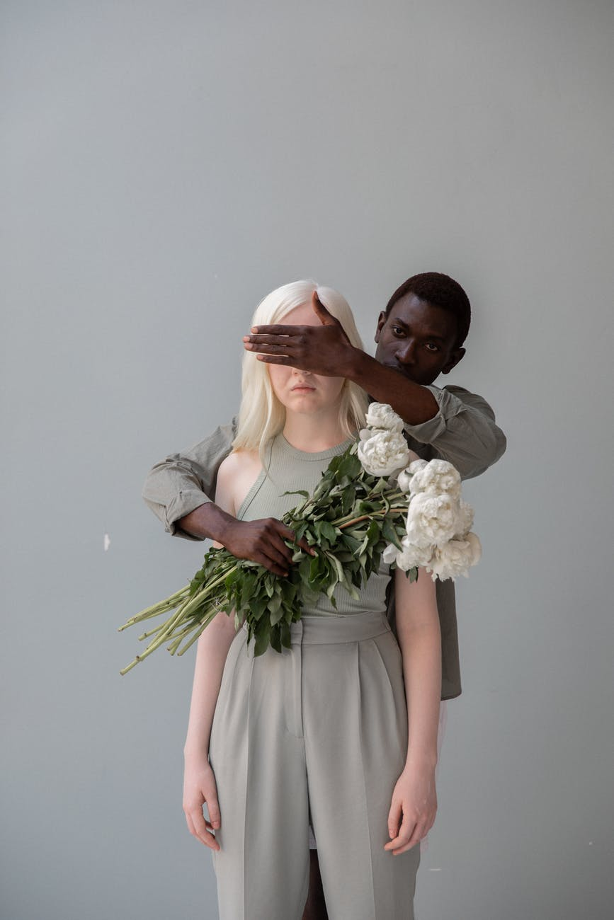 black man with flowers covering eyes of unrecognizable female beloved