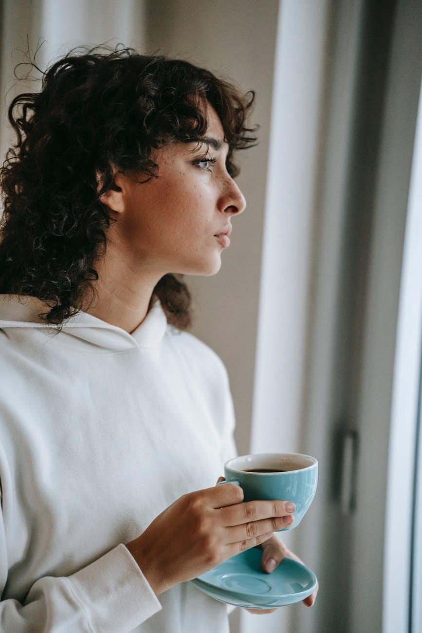 thoughtful woman drinking hot coffee at home